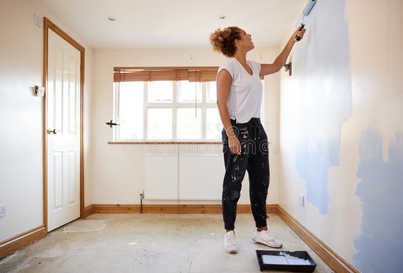 Kvinna som dekorerar rum i ny hem- måla vägg fotografering för bildbyråer