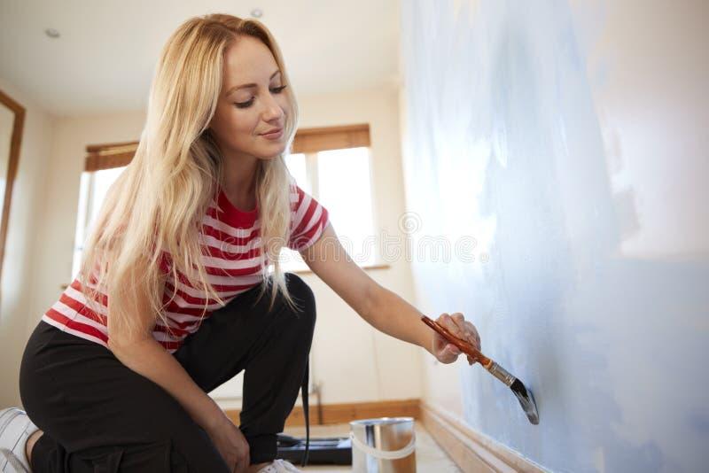 Kvinna som dekorerar rum i ny hem- måla vägg med borsten arkivfoton
