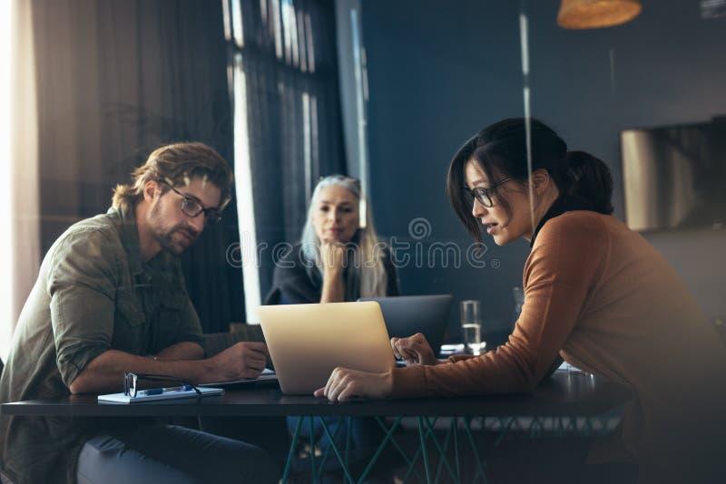 Kvinna som delar hennes idéer med bärbara datorn till kollegor royaltyfri fotografi