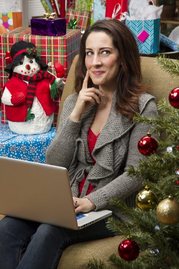 Kvinna som direktanslutet shoppar för julklappar royaltyfria bilder