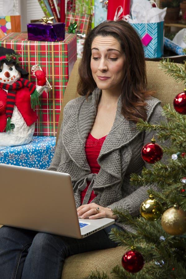 Kvinna som direktanslutet shoppar för julklappar arkivfoto