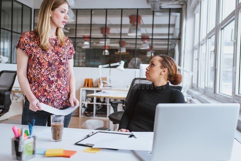Kvinna som diskuterar arbete med kollegan på kontoret royaltyfri bild