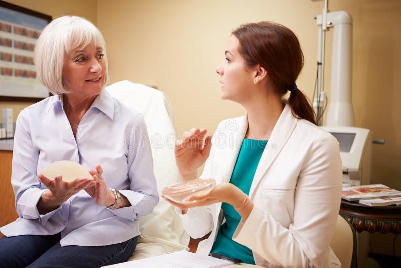 Kvinna som diskuterar bröststigande med den plast- kirurgen arkivfoto