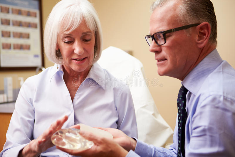 Kvinna som diskuterar bröststigande med den plast- kirurgen arkivbilder