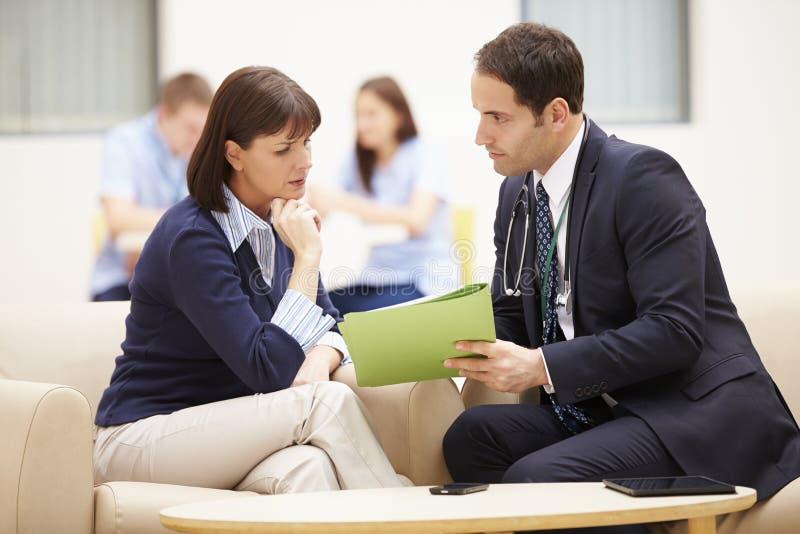 Kvinna som diskuterar provresultat med doktorn royaltyfria bilder