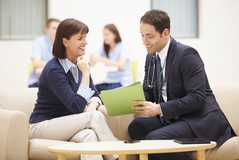 Kvinna som diskuterar provresultat med doktorn royaltyfri bild