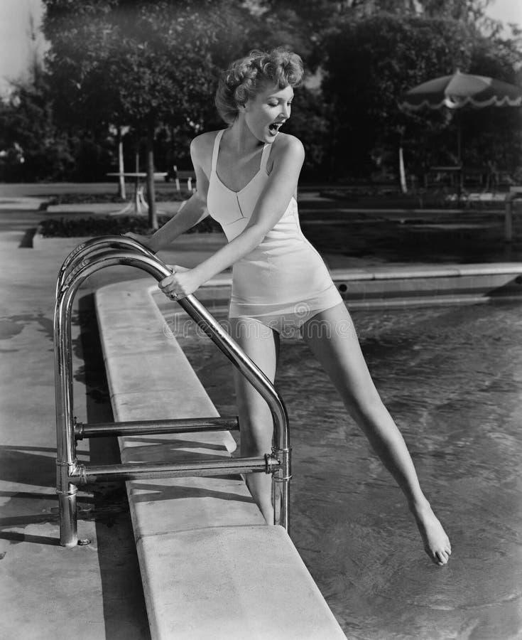 Kvinna som doppar tår i utomhus- simbassäng (alla visade personer inte är längre uppehälle, och inget gods finns Leverantörgarant royaltyfri foto