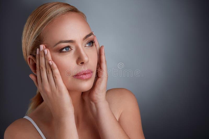 Kvinna som drar åt hud på framsida för att göra dig att se mer ung royaltyfri bild