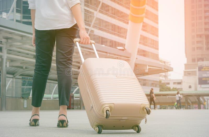 Kvinna som drar resväskan i modern stad; tappningsignalstil royaltyfri foto