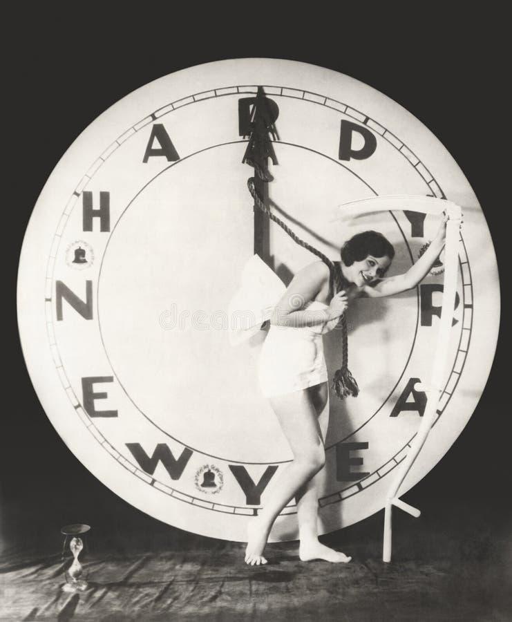 Kvinna som drar timmehanden av den jätte- klockan på nyårsafton royaltyfri foto