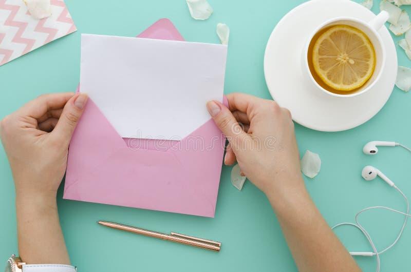 Kvinna som dricker örtte Hand som rymmer ett rosa kuvert med den tomma pappers- bokstavsmodellen på tiffany bakgrund för mintkara royaltyfria foton
