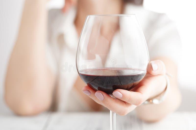 Kvinna som dricker alkohol på vit bakgrund Fokus på vinexponeringsglas royaltyfria bilder