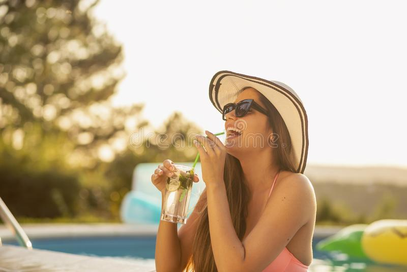 Kvinna som dricker coctailar vid pölen royaltyfria foton