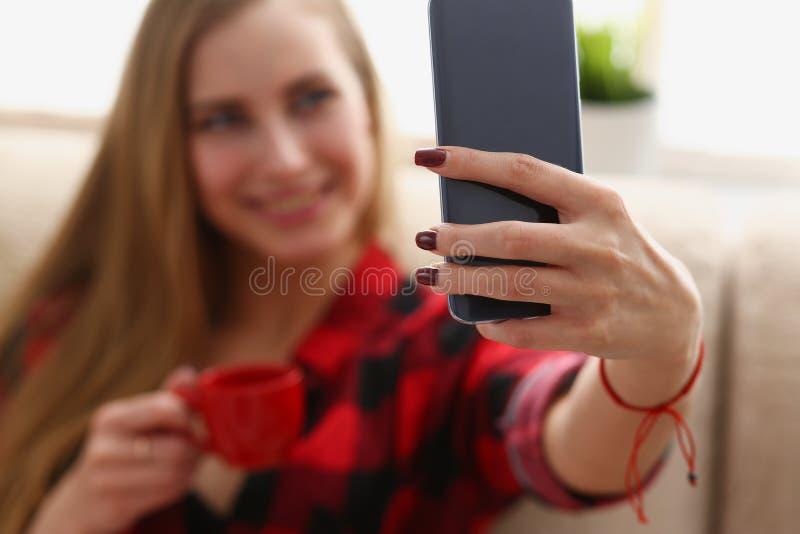 Kvinna som dricker coffe och blick på bärbara datorn arkivfoton