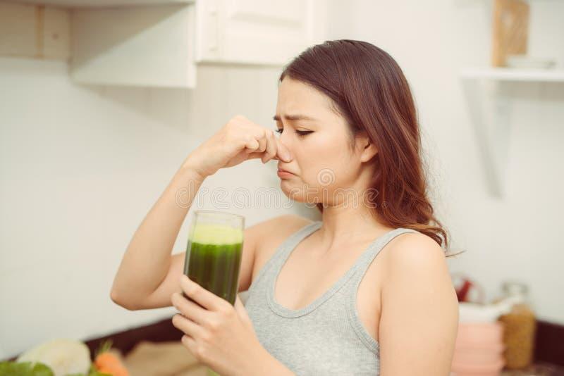 Kvinna som dricker den ?ckliga gr?na smoothien, bokslutn?san, den d?liga lukten och smak royaltyfria foton