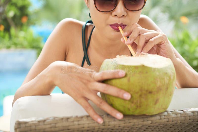 Kvinna som dricker den förnyande kokosnötcoctailen royaltyfria foton