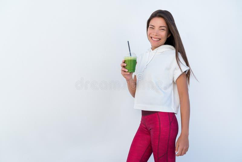 Kvinna som dricker den gr?na detoxsmoothien f?r gr?nsak royaltyfri foto