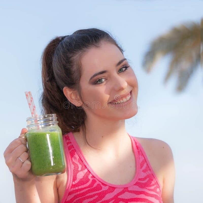 Kvinna som dricker den sunda smoothien royaltyfria bilder