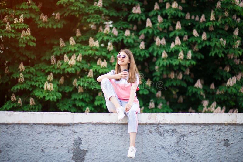 Kvinna som dricker den utomhus- tyckande om naturen f?r varmt kaffe under ferie i sommardag med kastanjen p? bakgrund, feriebegre arkivfoto