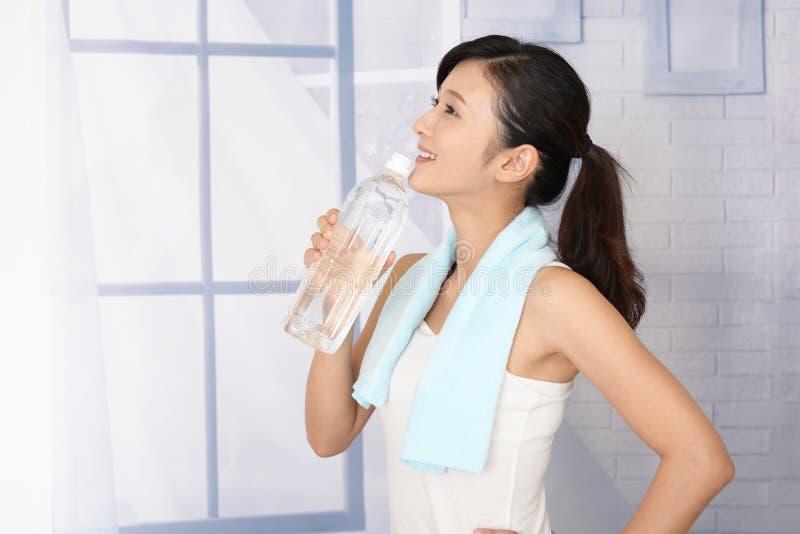 Kvinna som dricker en flaska av vatten royaltyfri foto