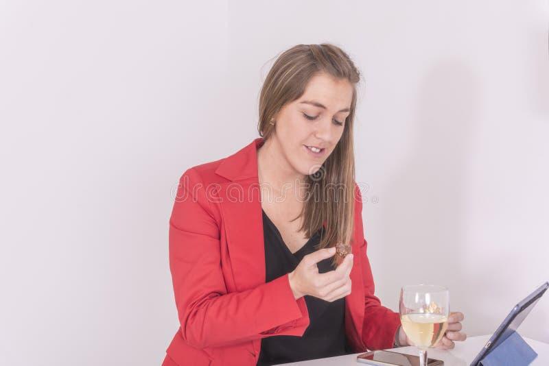 Kvinna som dricker ett exponeringsglas av bränd mandel för vitt vin och choklad royaltyfria foton