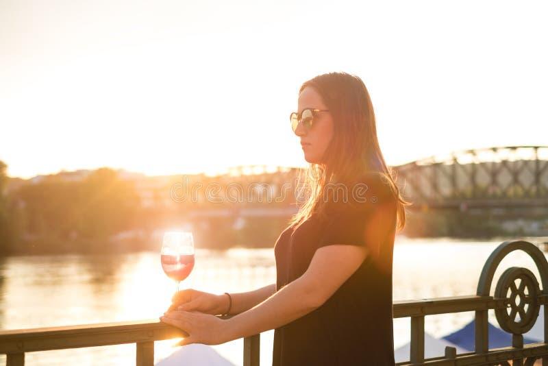 Kvinna som dricker ett vin i staden under en solnedgång glass rött vin Begrepp av fri tid i staden och drickaalkoholen royaltyfri fotografi