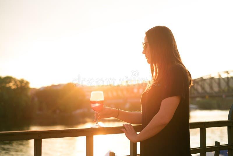 Kvinna som dricker ett vin i staden under en solnedgång glass rött vin Begrepp av fri tid i staden och drickaalkoholen fotografering för bildbyråer