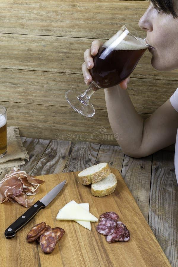 Kvinna som dricker från ett exponeringsglas av öl fotografering för bildbyråer