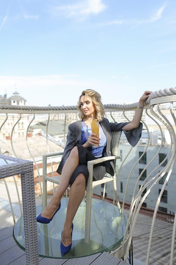 Kvinna som dricker fruktsaft på kafét på balcone i Europa arkivfoton