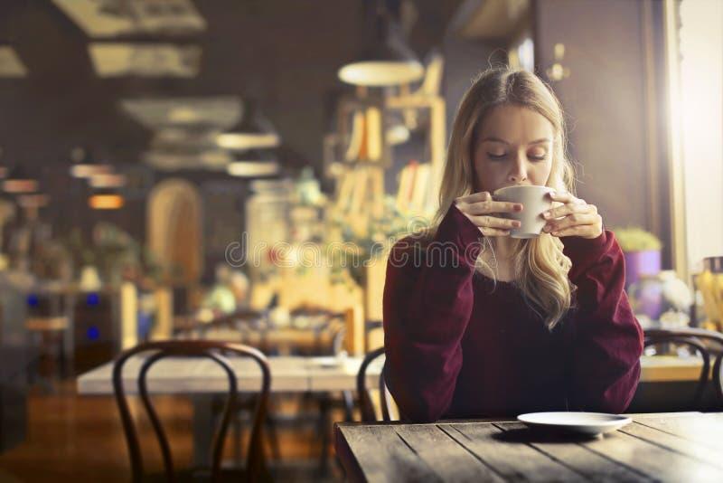 Kvinna som dricker i ett kafé royaltyfri fotografi