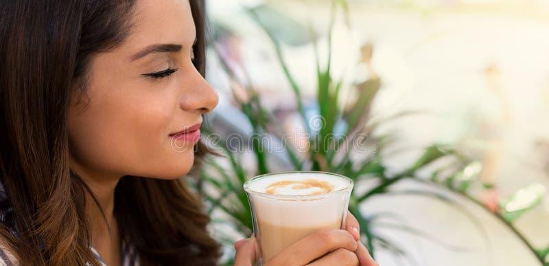 Kvinna som dricker kaffe i kafét som tycker om hennes morgon arkivbilder