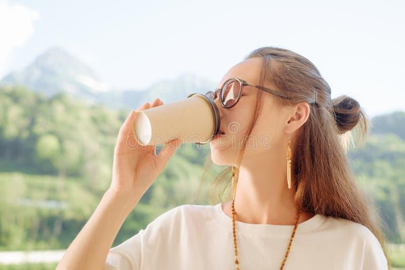 Kvinna som dricker kaffe i sommarmorgon royaltyfria bilder