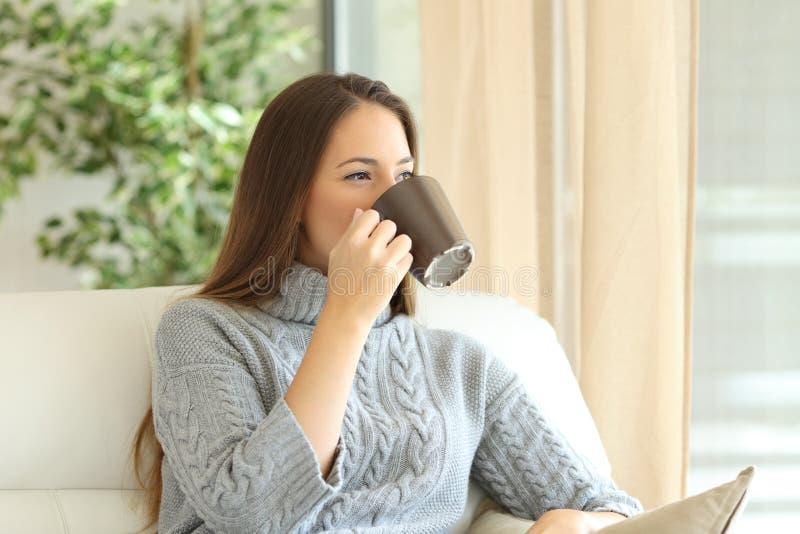 Kvinna som dricker kaffe i vinter royaltyfri fotografi