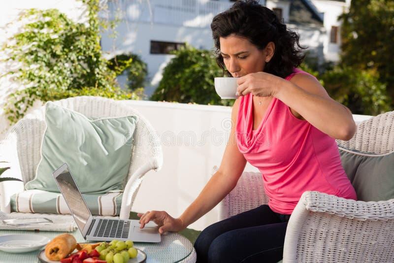 Kvinna som dricker kaffe, medan genom att använda bärbara datorn på kafét fotografering för bildbyråer
