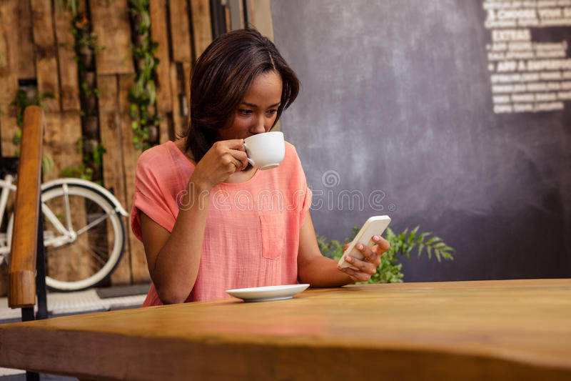 Kvinna som dricker kaffe och använder smartphonen royaltyfria bilder