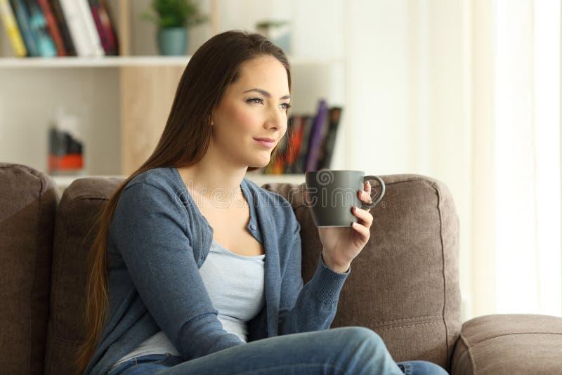 Kvinna som dricker kaffe och ser bort på en soffa fotografering för bildbyråer