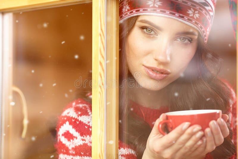 Kvinna som dricker kaffe och ser ut ur fönstret på vintern da royaltyfri bild