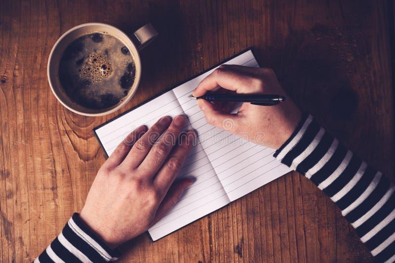 Kvinna som dricker kaffe och skriver en dagbokanmärkning arkivbilder