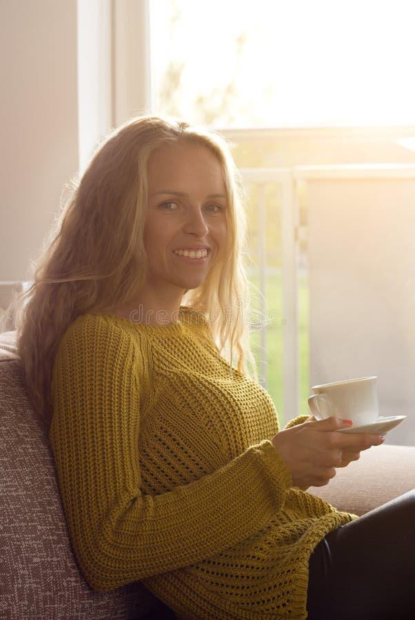 Kvinna som dricker kaffe på soffan bredvid fönster arkivbilder