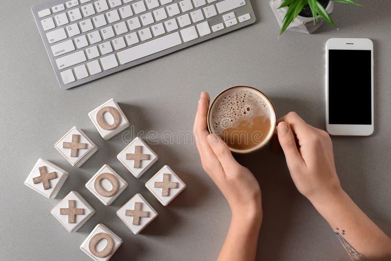 Kvinna som dricker kaffe på tabellen med kuber för datortangentbord och för muskelryckningtac-tå, bästa sikt arkivbilder