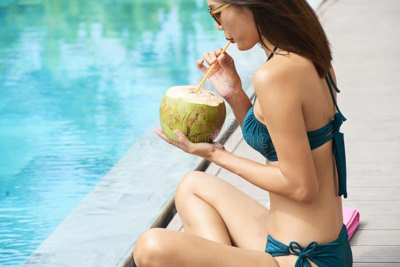 Kvinna som dricker kokosnötdrinken royaltyfria foton