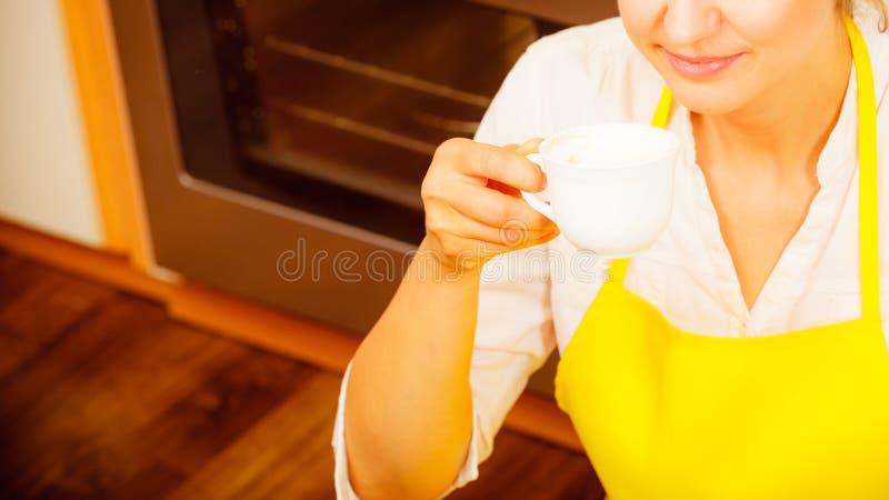 Kvinna som dricker koppen kaffe i kök royaltyfria foton