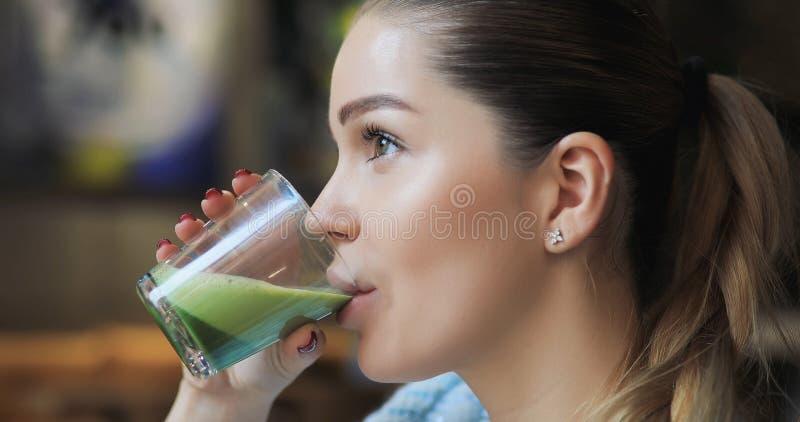 Kvinna som dricker matchalatte i kafé royaltyfria bilder