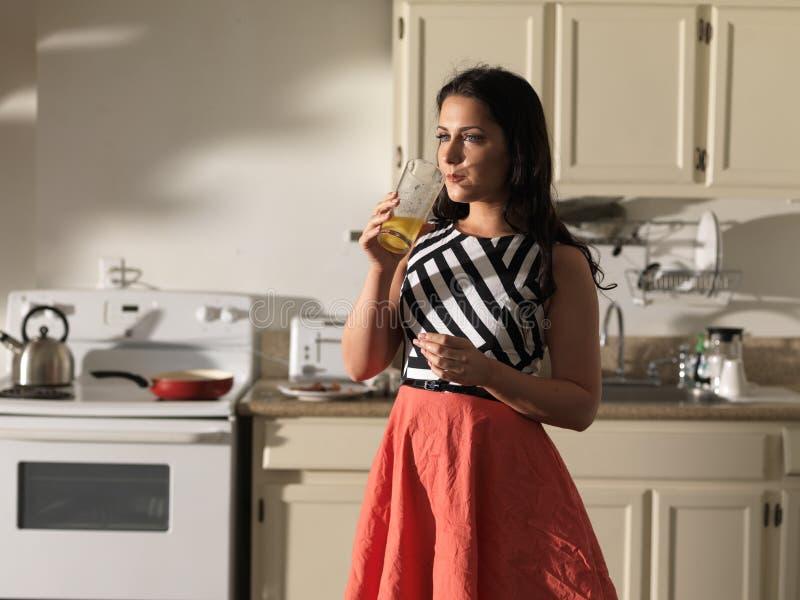 Kvinna som dricker orange fruktsaft i kök som bär den retro klänningen arkivbild