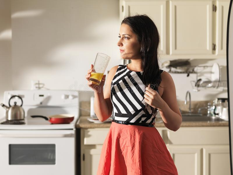 Kvinna som dricker orange fruktsaft i kök som bär den retro klänningen royaltyfria foton