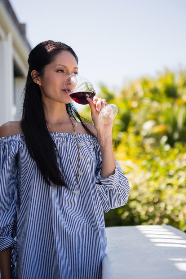 Kvinna som dricker rött vin, medan stå i balkong arkivfoto