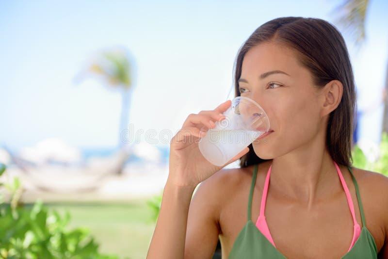 Kvinna som dricker sötvatten eller limefrukt Juice At Beach arkivbilder