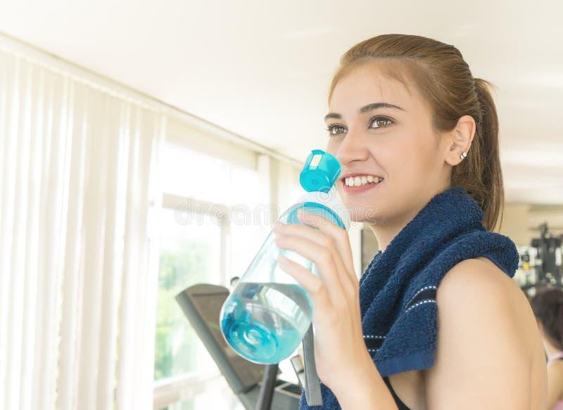 Kvinna som dricker sötvatten, medan utarbeta i konditionidrottshall arkivfoton
