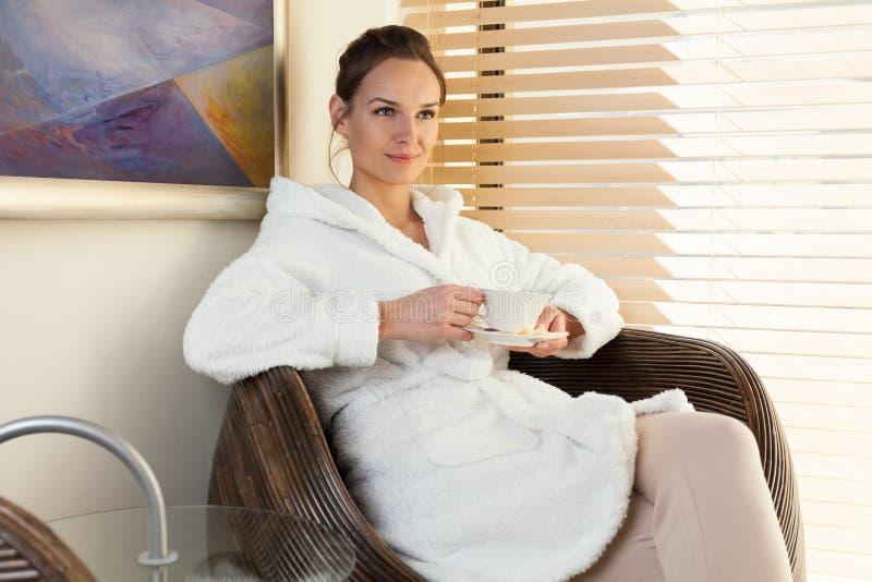 Kvinna som dricker te i väntande rum på brunnsortmitten arkivfoto