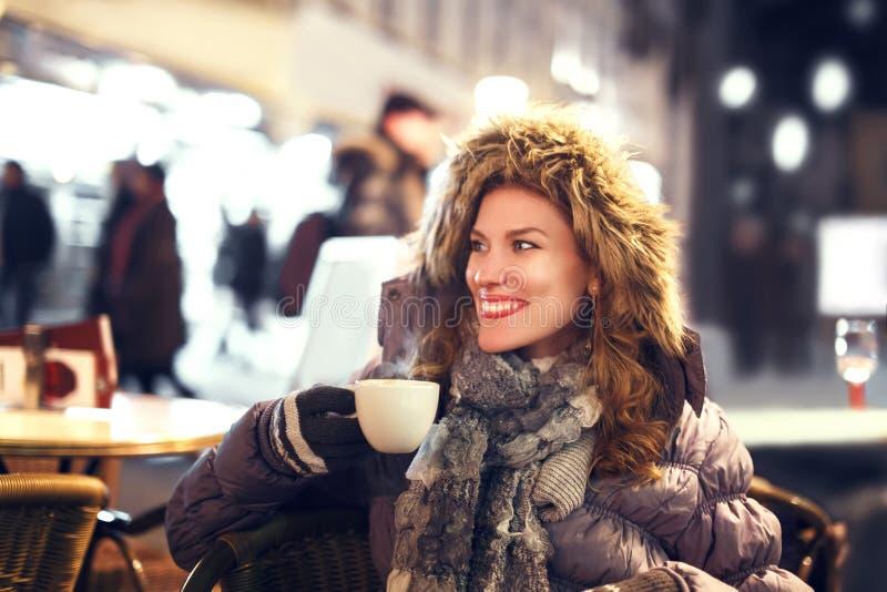 Kvinna som dricker varmt kaffe som är utomhus- på vintern arkivfoton
